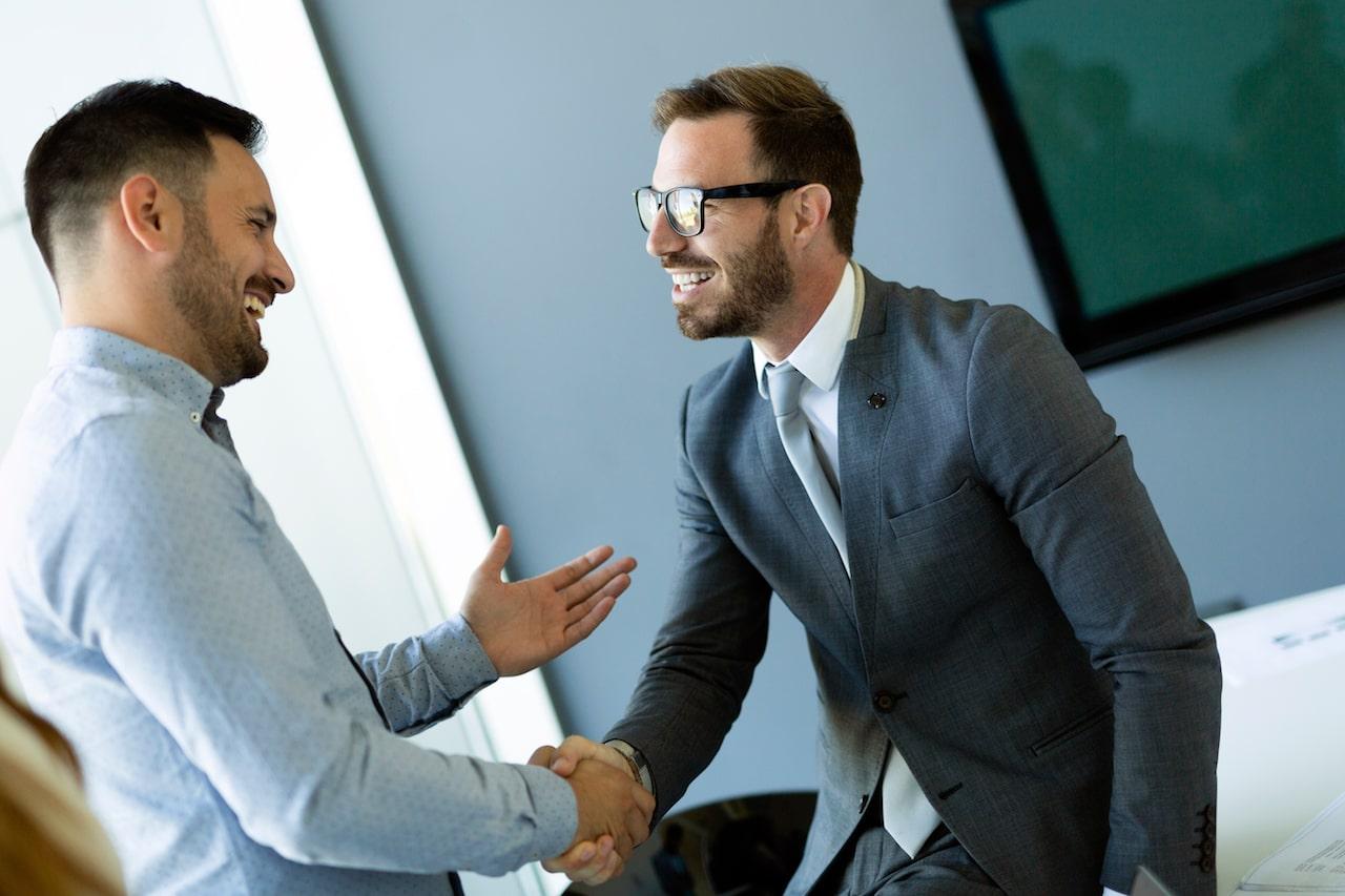 Businessmen Shaking Hands in Office - SolVibrations