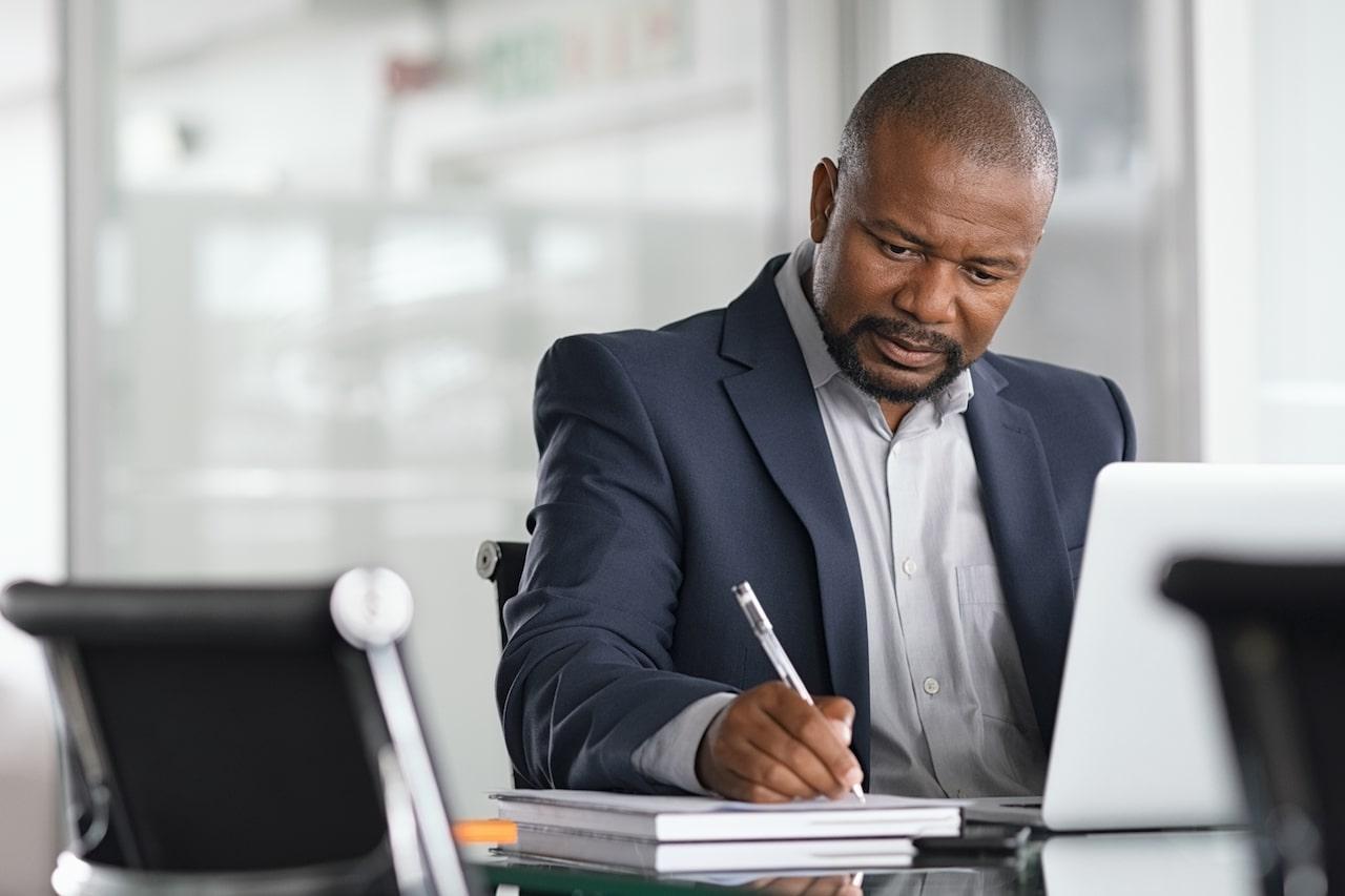 Mature Businessman Writing-on Documents - SolVibrations